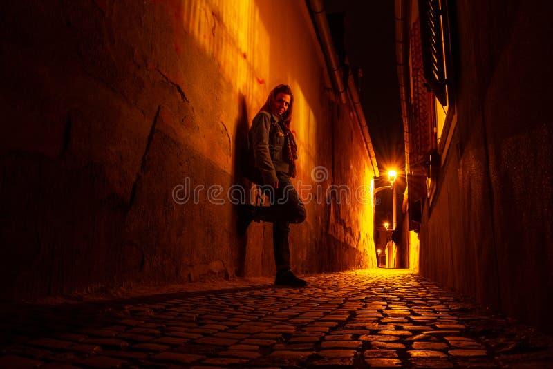 Retrato temperamental de uma jovem mulher em uma passagem urbana estreita, na noite, ao lado dos obturadores da janela aberta, em fotografia de stock royalty free