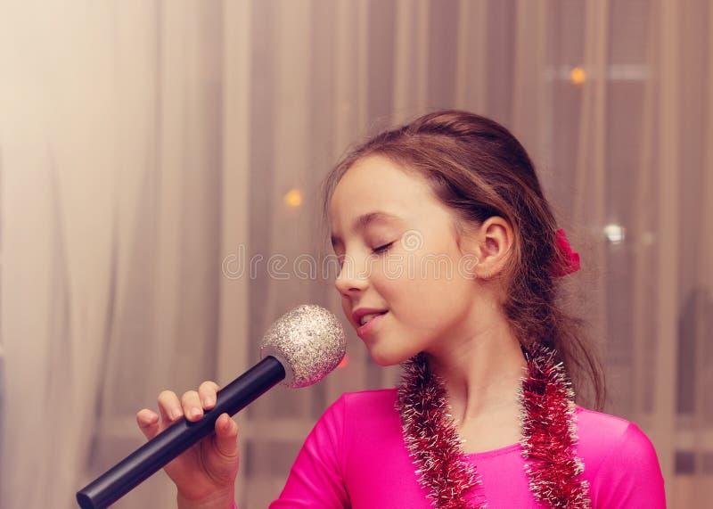 Retrato tonificado da menina bonito que canta em um microfone fotografia de stock royalty free