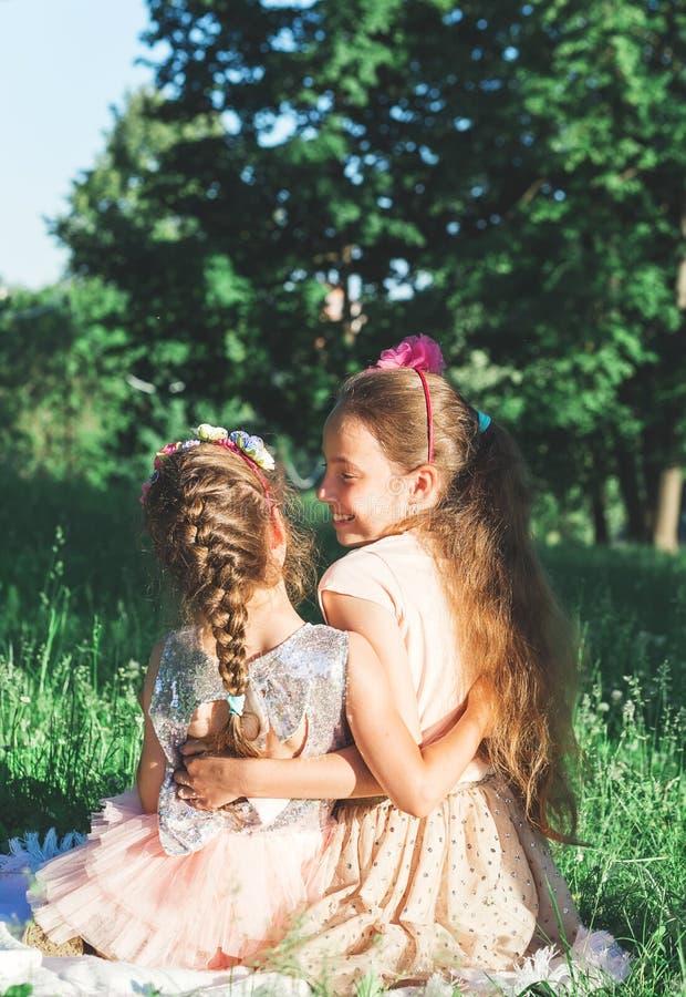Retrato tonificado de duas meninas felizes que abraçam e que gastam fotos de stock