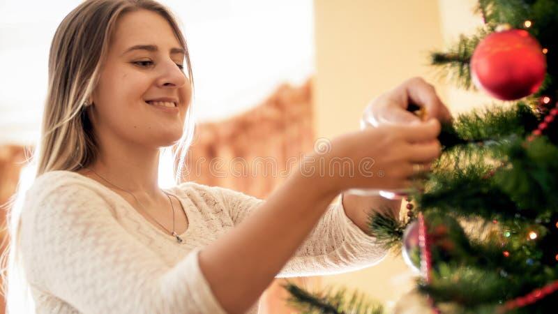 Retrato tonificado do close up da jovem mulher que decora a árvore de Natal com quinquilharias e grânulos fotografia de stock