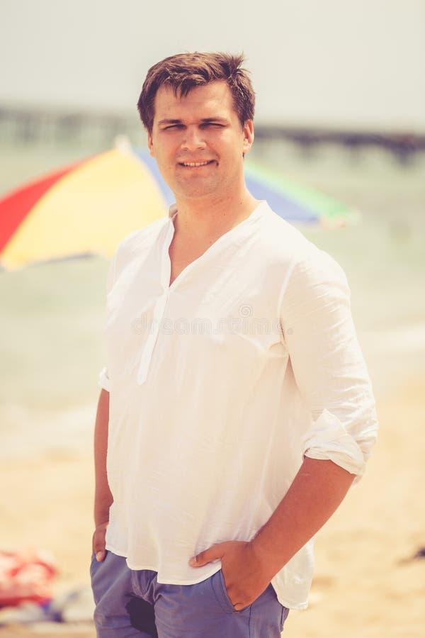 Retrato tonificado do homem considerável de sorriso que levanta na praia ensolarada foto de stock