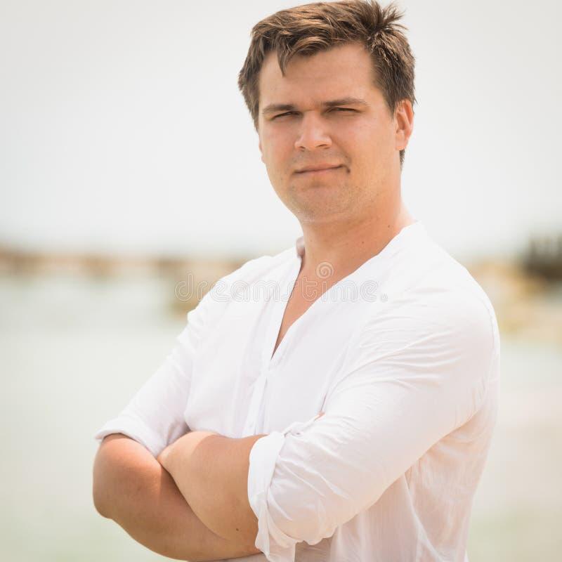 Retrato tonificado do homem considerável na camisa branca na praia fotos de stock