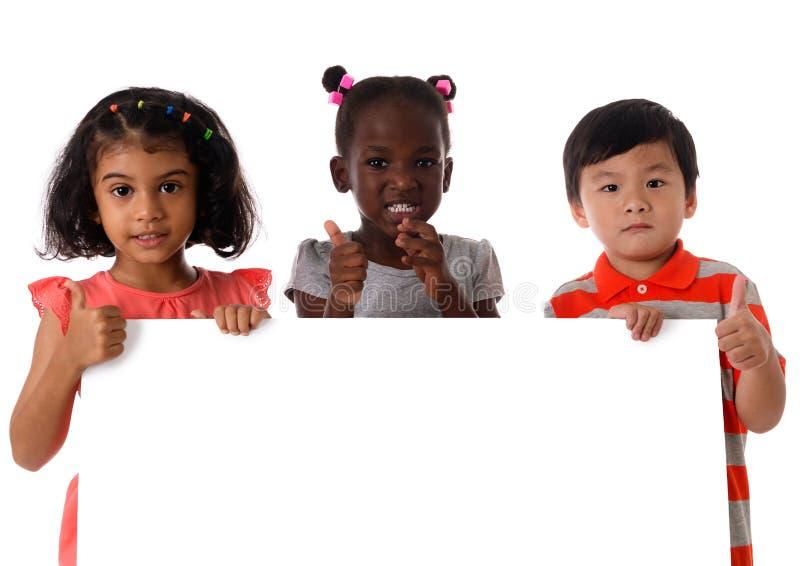 Retrato três de crianças multirraciais no estúdio com placa branca Isolado fotos de stock