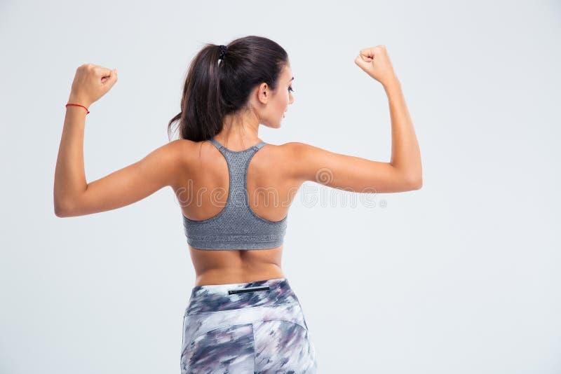 Retrato traseiro da vista de uma mulher da aptidão que mostra seu bíceps fotos de stock royalty free