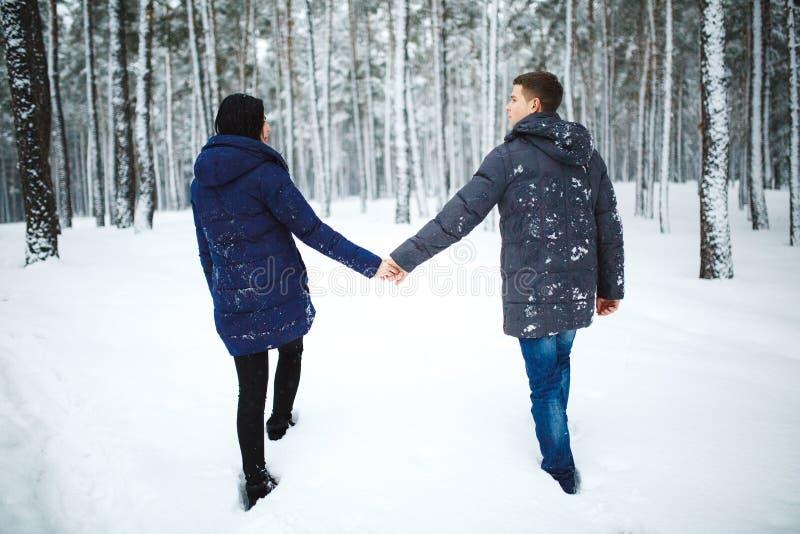 Retrato trasero al aire libre de la visión del hombre alegre y de la muchacha bonita que disfrutan de las nevadas en bosque del i imagen de archivo libre de regalías