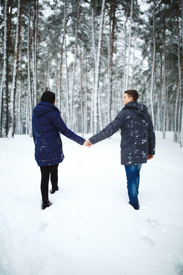 Retrato trasero al aire libre de la visión del hombre alegre y de la muchacha bonita que disfrutan de las nevadas en bosque del i imagen de archivo