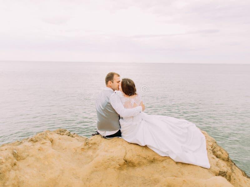 Retrato trasero romántico de los pares que se besan mientras que se sienta en el acantilado en el fondo del mar durante la puesta foto de archivo