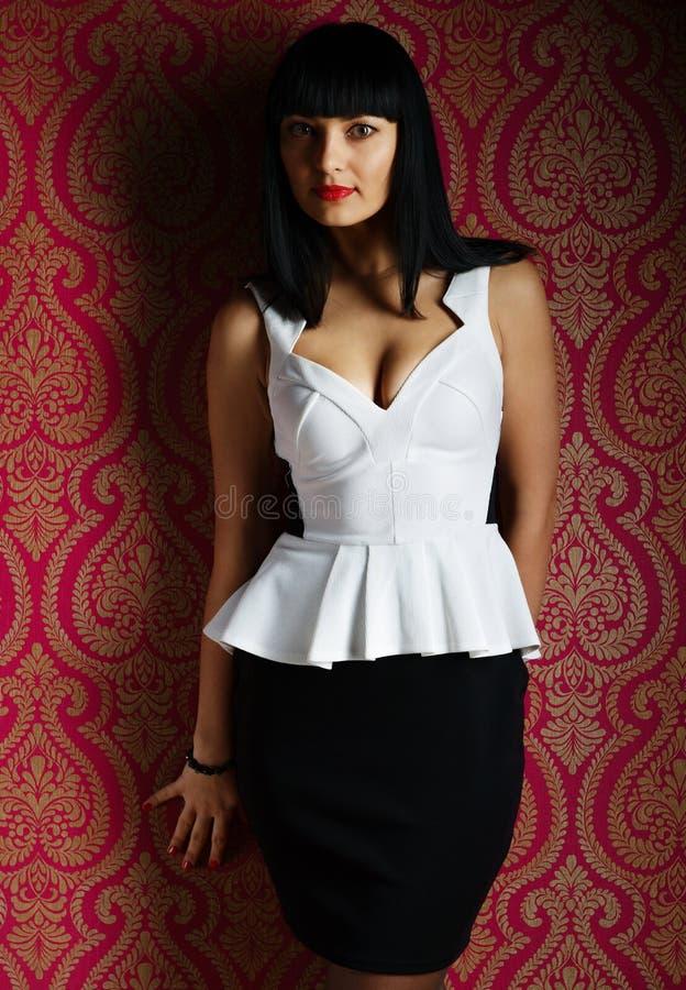 Retrato triguenho da mulher do encanto no vestido preto e branco foto de stock royalty free
