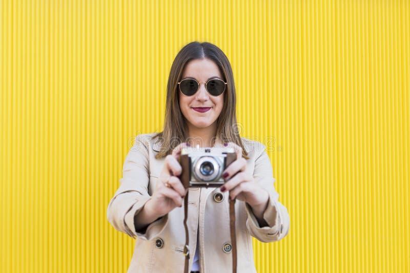 Retrato uma mulher bonita nova que guarda uma câmera do vintage sobre y imagens de stock