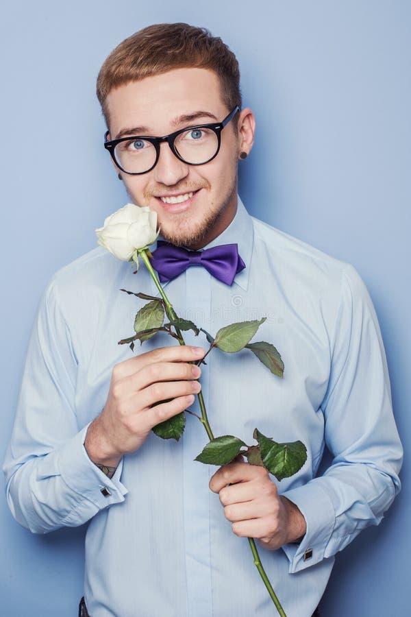Retrato un hombre joven en camisa azul con la rosa del blanco Fecha, cumpleaños, tarjeta del día de San Valentín imágenes de archivo libres de regalías
