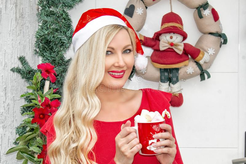 Retrato Una muchacha rubia joven hermosa en el casquillo de Papá Noel se está colocando en la puerta principal, adornada con una  foto de archivo