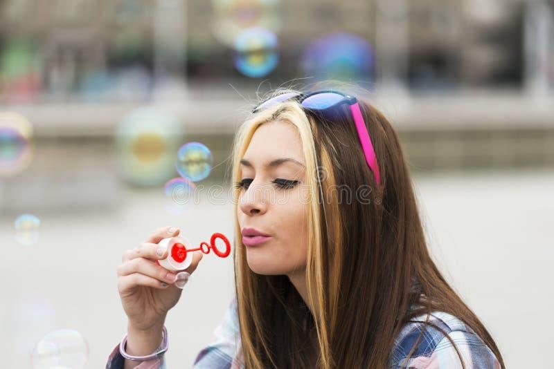 Retrato urbano da moça bonita que joga com bolhas imagem de stock