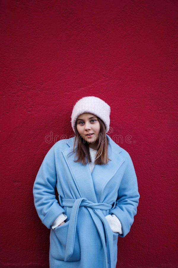 Retrato vertical da menina agradável do moderno que veste o revestimento morno do casualblue e o chapéu de lã em um fundo vinous  fotografia de stock royalty free
