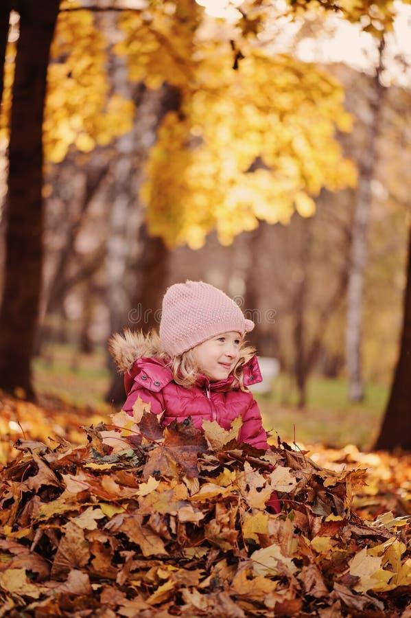 Retrato vertical da menina de sorriso bonito da criança que tem o divertimento na caminhada ensolarada do outono imagem de stock
