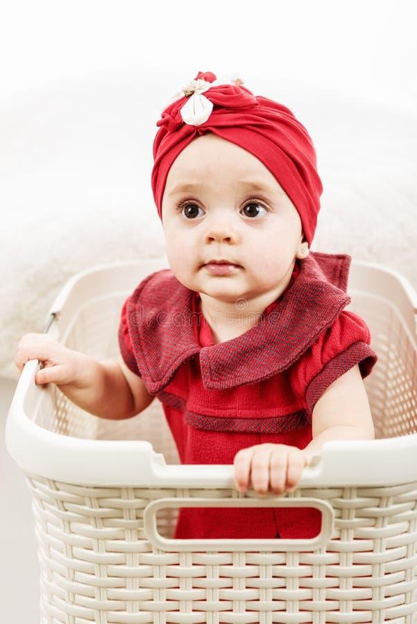 Retrato vertical da menina do bebê de um ano dentro da cesta de lavanderia fotos de stock
