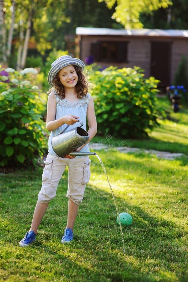 Retrato vertical da menina feliz da criança no chapéu do jardineiro que joga com lata molhando foto de stock