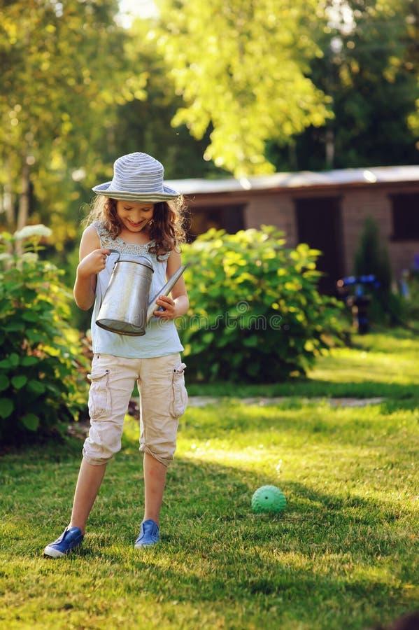 Retrato vertical da menina feliz da criança no chapéu do jardineiro que joga com lata molhando fotografia de stock