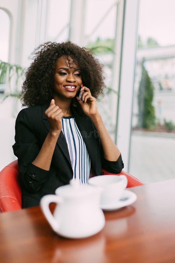 Retrato vertical da mulher afro-americana encantador que fala no telefone celular no café imagens de stock