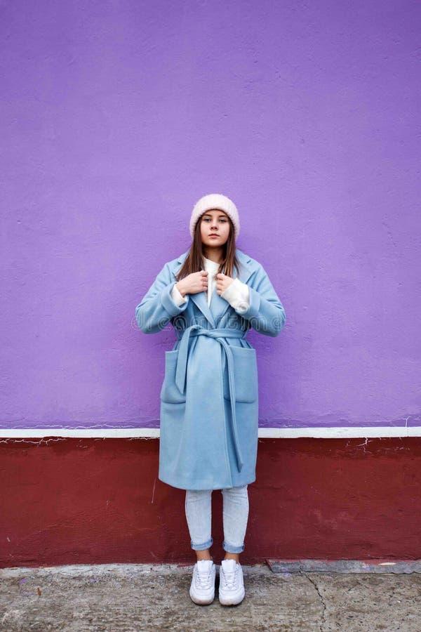 Retrato vertical de la hembra caucásica agradable con el pelo marrón, la capa casual azul que lleva y el sombrero de lana calient fotografía de archivo libre de regalías