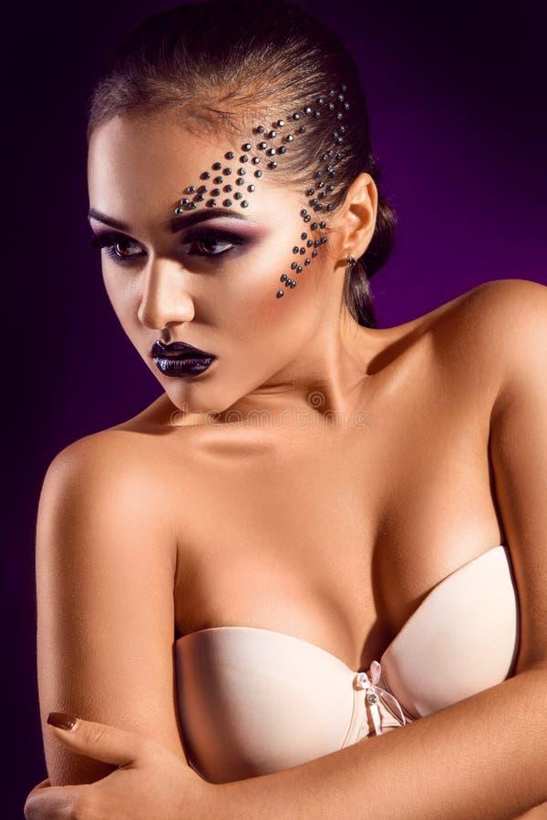 Retrato vertical de la muchacha adulta sensual con los diamantes en cara adentro imagen de archivo