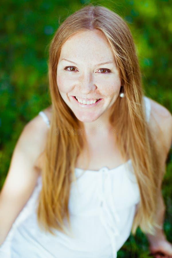 Muchacha sonriente pelirroja que se sienta en la hierba fotografía de archivo libre de regalías