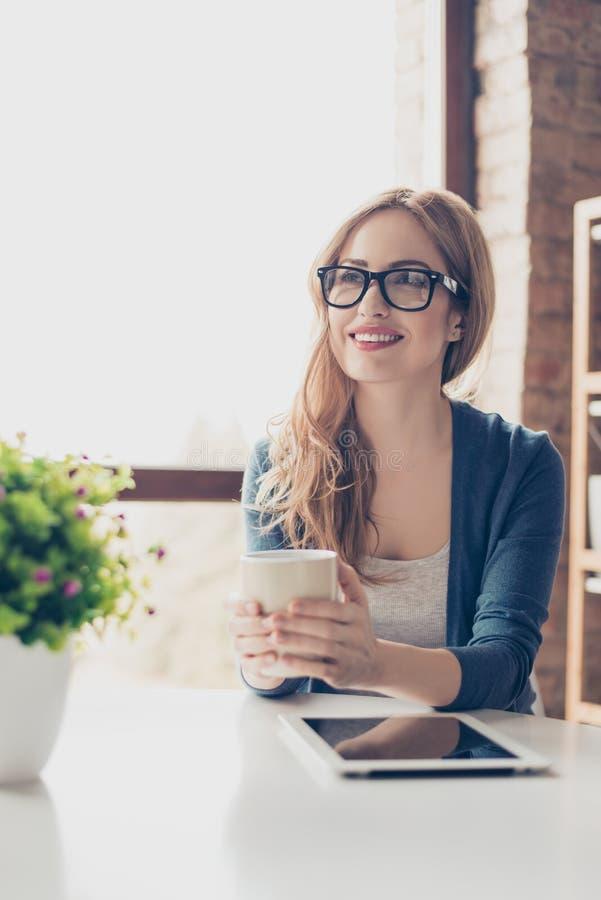 Retrato vertical de la mujer sonriente que se sienta en un café que bebe el co imágenes de archivo libres de regalías
