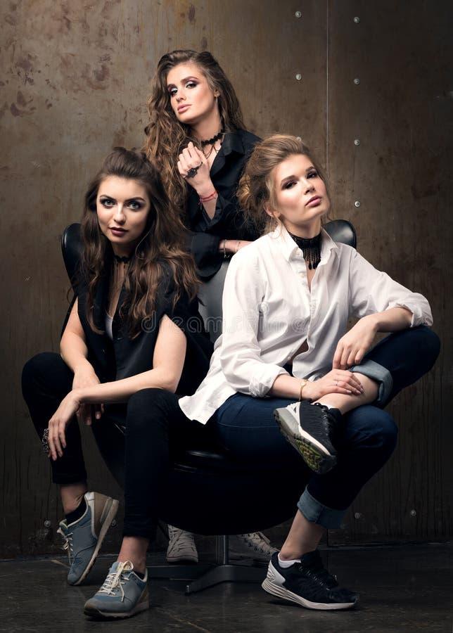 Retrato vertical de tres mujeres jovenes hermosas que presentan en una silla imagen de archivo libre de regalías
