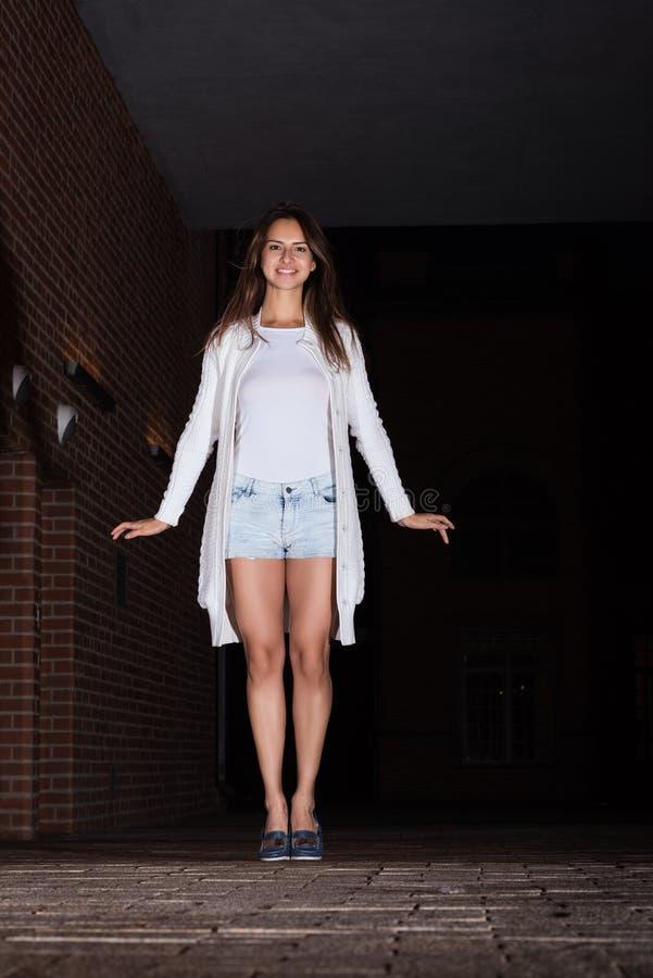 Retrato vertical de uma jovem mulher bonito que anda na rua da cidade da noite imagens de stock royalty free