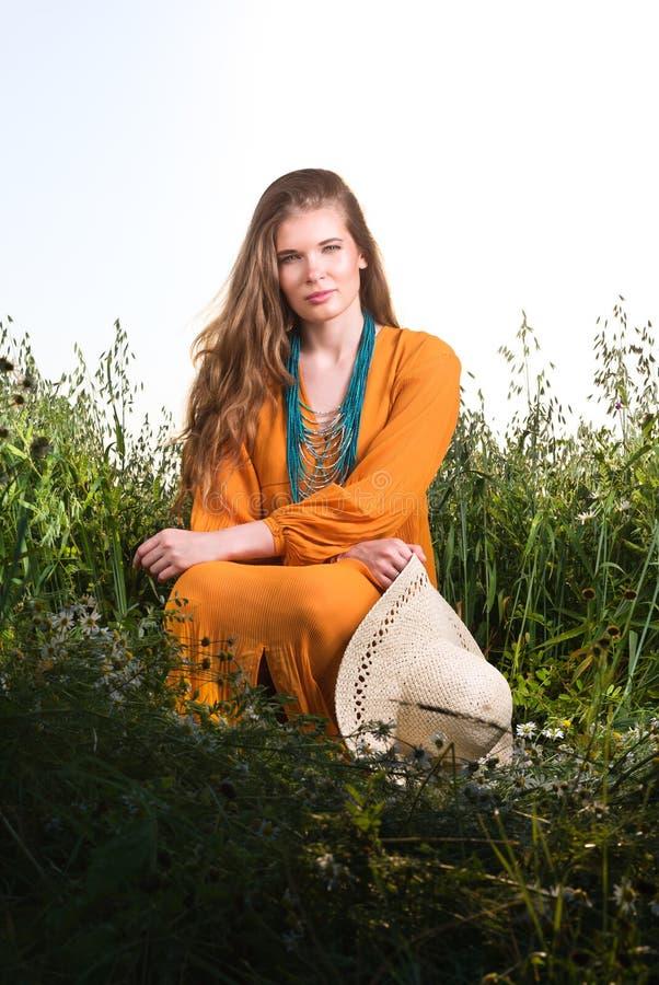 Retrato vertical de uma jovem mulher que senta-se na grama alta Vestido vermelho foto de stock