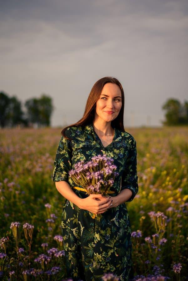 Retrato vertical de uma morena em um prado da flor no por do sol que guarda o ramalhete de flores selvagens imagens de stock royalty free
