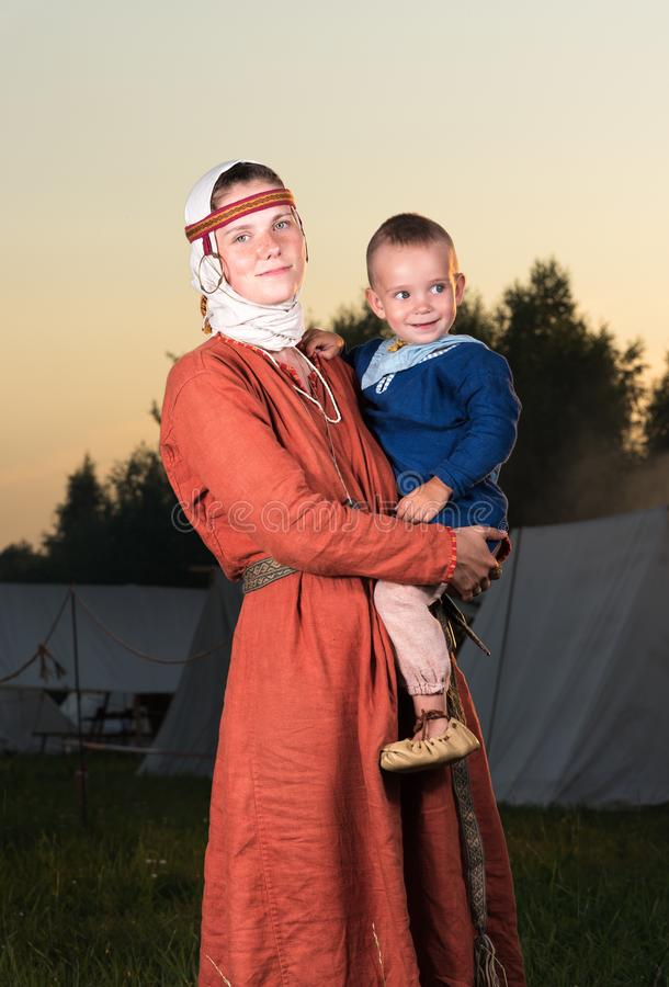 Retrato vertical de uma mulher eslavo com uma criança na história do traje imagens de stock