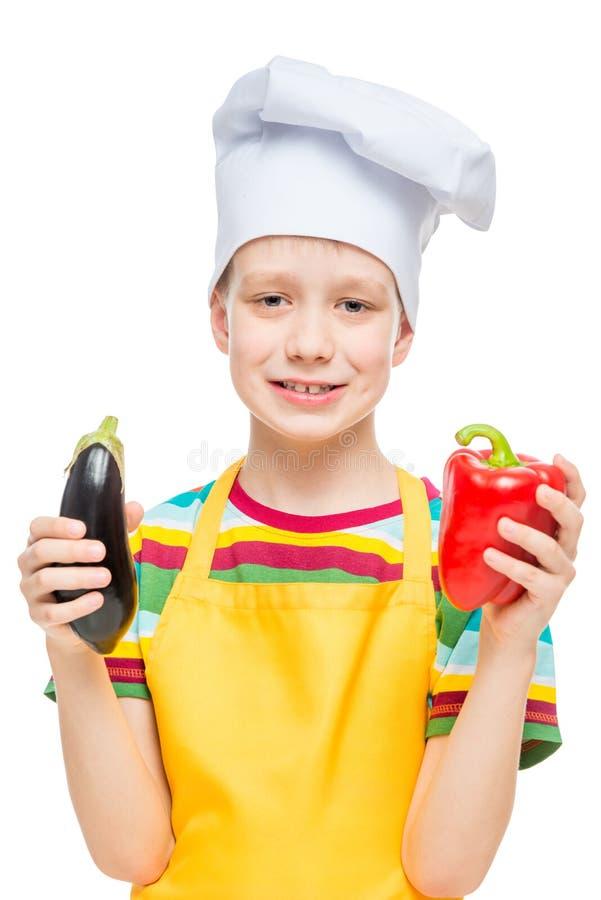 Retrato vertical de un niño en un sombrero del cocinero con pimienta y berenjena en un blanco imágenes de archivo libres de regalías