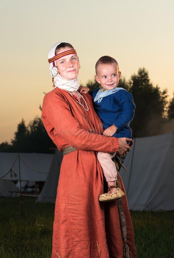 Retrato vertical de una mujer eslava con un niño en historia del traje imagenes de archivo
