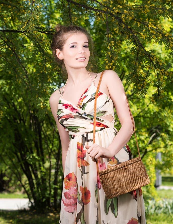 Retrato vertical de una mujer joven hermosa con un bolso en el parque imágenes de archivo libres de regalías