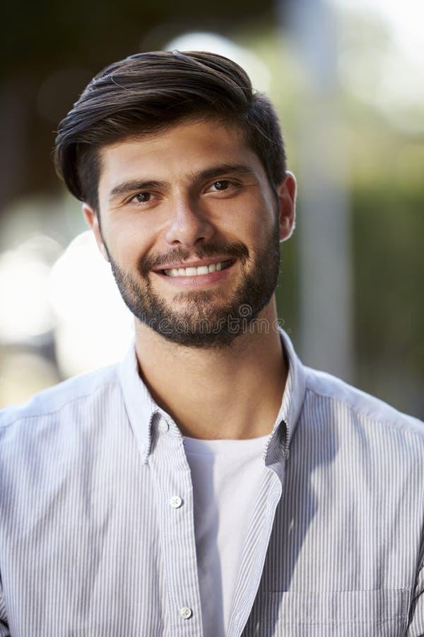 Retrato vertical do homem novo farpado que senta-se fora fotos de stock