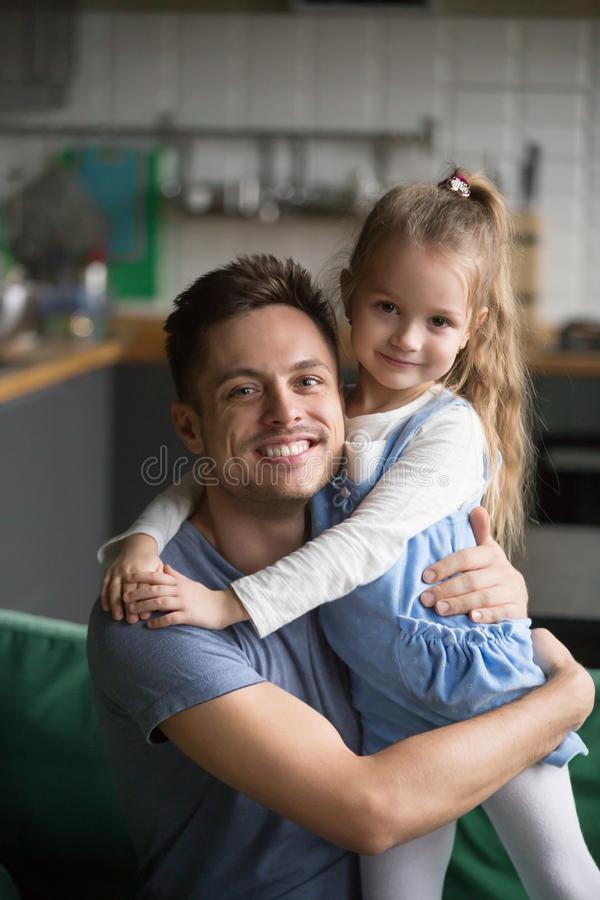 Retrato vertical do pai de abraço da filha feliz da criança em casa imagens de stock royalty free