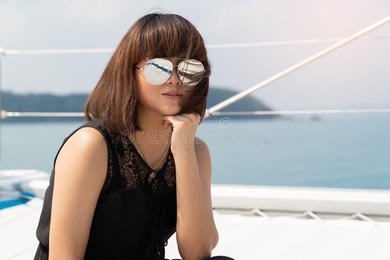 Retratos bonitos asiáticos da mulher no yacth luxuoso no mar e no b foto de stock