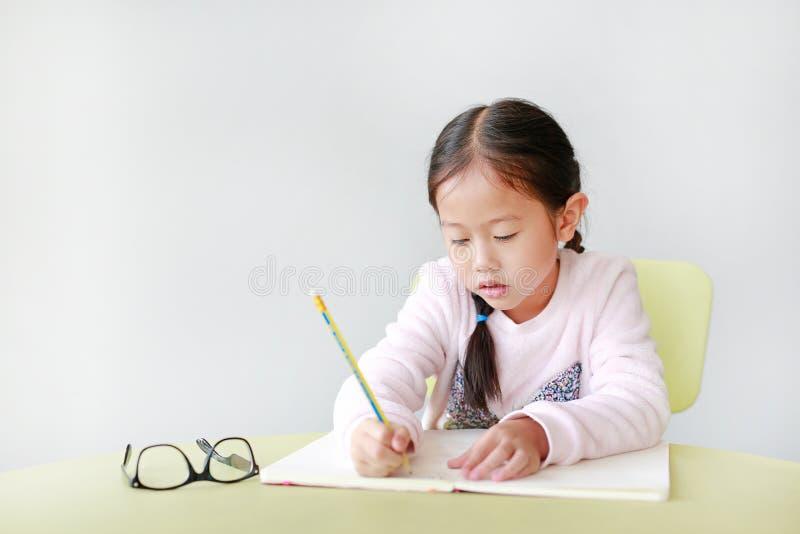 Retratos de garotinha asiática escrevem em um livro ou notebook com lápis sentado em uma cadeira de criança e mesa contra o branc foto de stock royalty free