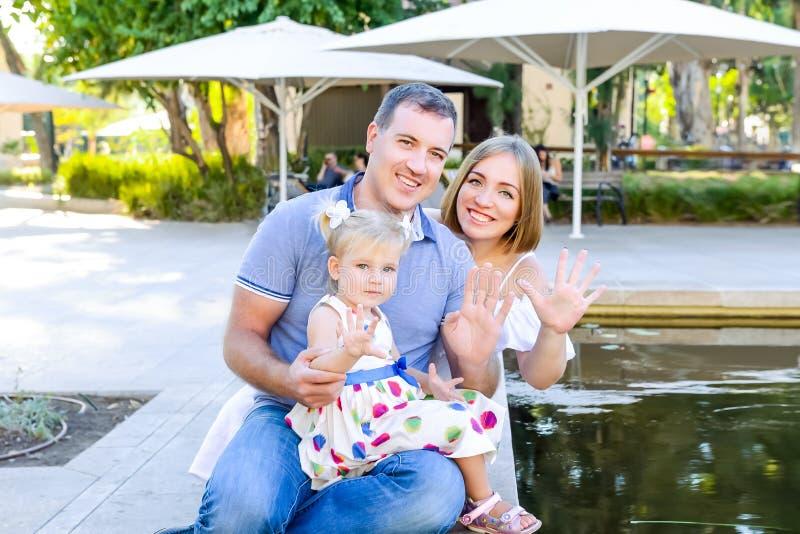 Retratos de la familia feliz de tres - madre, padre e hija agitando sus manos en la cámara que se sienta cerca de la charca en el imágenes de archivo libres de regalías