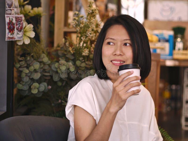 Retratos de la mujer asiática que sostienen una taza de café que mira a su mano derecha en cafetería acogedora fotografía de archivo libre de regalías
