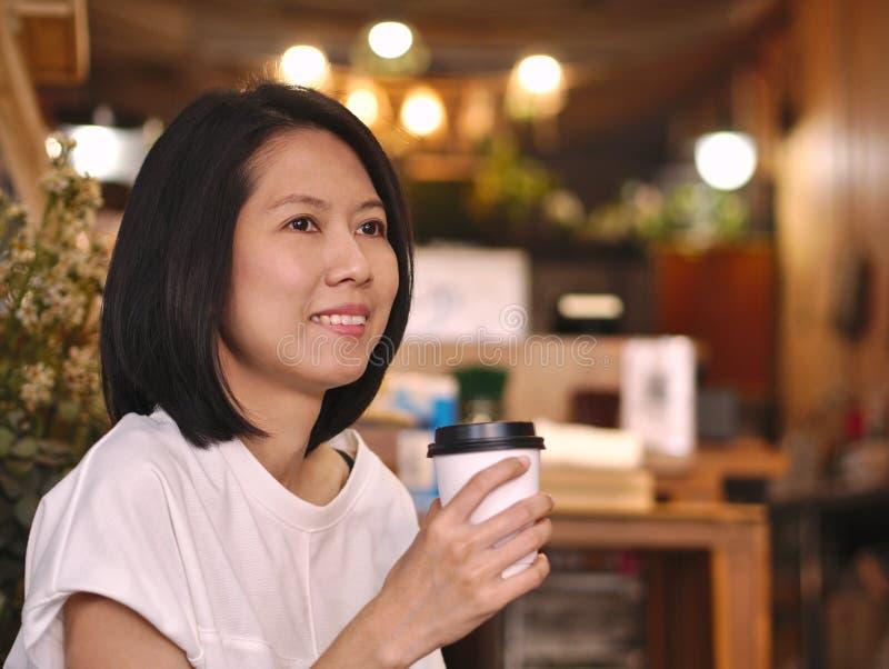 Retratos de la mujer asiática que sostienen una taza de café que mira a su mano izquierda en cafetería acogedora imagen de archivo libre de regalías