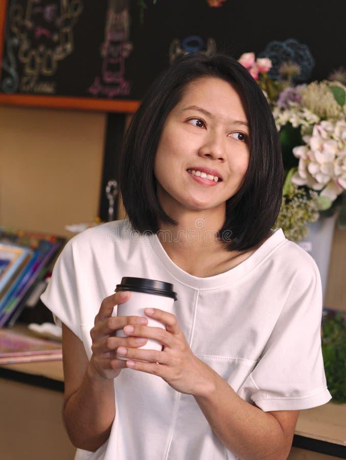 Retratos de la mujer asiática que sostienen una taza de café por dos manos que miran a su mano izquierda en cafetería acogedora imagen de archivo libre de regalías