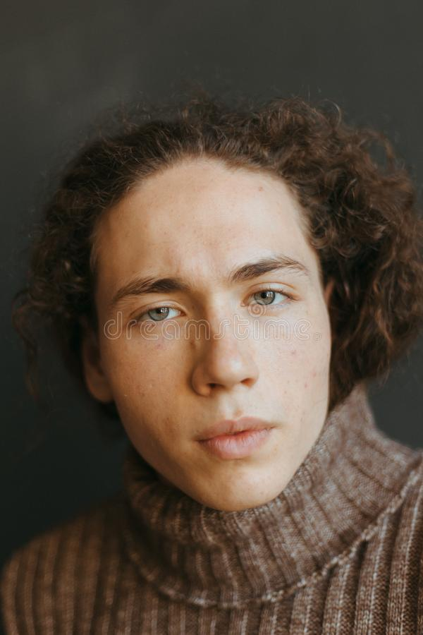 Retratos de um indivíduo com uma aparência atrativa, um cabelo encaracolado e uma roupa à moda imagens de stock royalty free