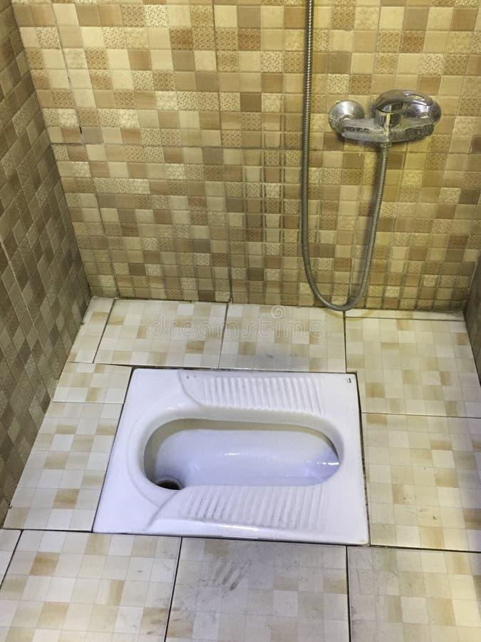 Retrete agazapado asiático en lavabo tejado foto de archivo
