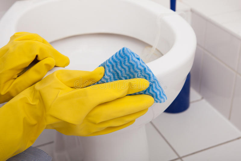 Retrete de la limpieza de la mano de la persona fotos de archivo
