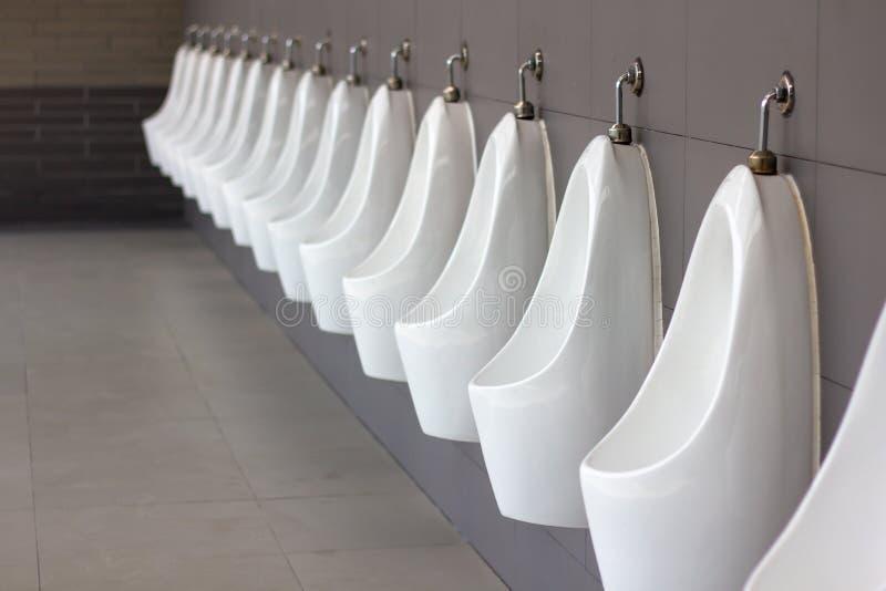 Retrete público de los hombres, lavabo para masculino Cuarto de baño del wc del retrete de los señores Fila de orinales blancos a foto de archivo