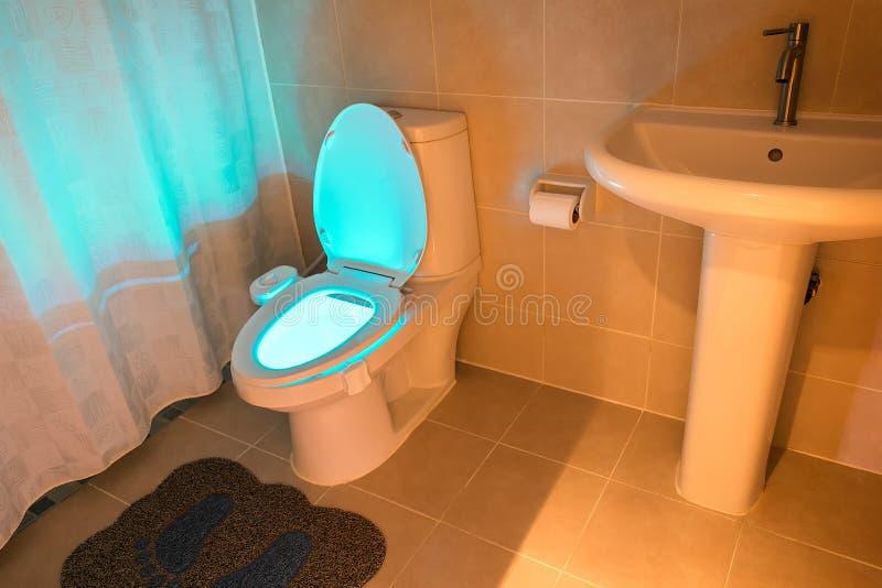 Retrete que brilla intensamente en un cuarto de baño moderno estándar imagenes de archivo