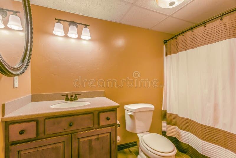 Retrete y vanidad con el gabinete de madera y el espejo redondo dentro de un cuarto de baño foto de archivo