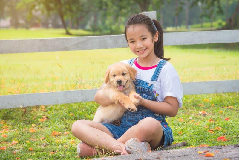 Retriever εκμετάλλευσης κοριτσιών χρυσό λίγο σκυλί στο πάρκο στοκ εικόνες