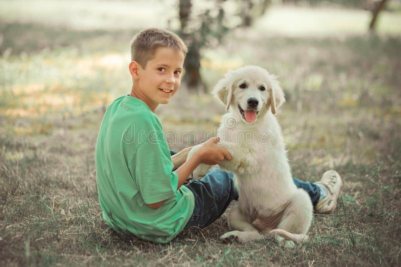 Retriever pup Lovely scene handsom teen boy enjoying summer time vacation with best friend dog ivory white labrador puppy.Happy ai. Rily careless childhood life stock photo